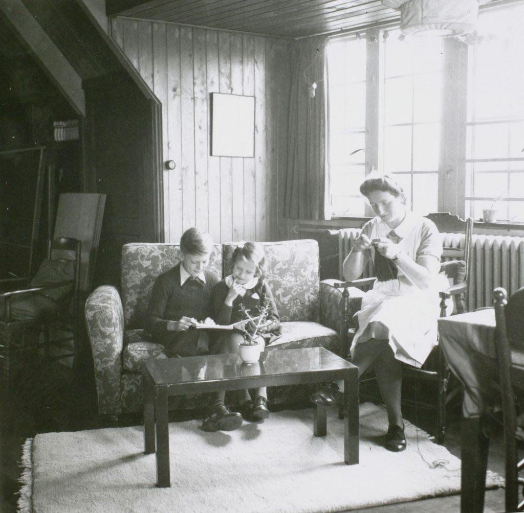 Kinderen van F.G. Waller in de woonkamer, onder toeziend oog van hun verzorgster, 1941, foto Peter Odijk (TMS 18657)