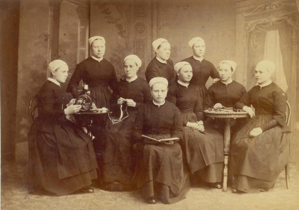 Weesmeisjes van het Weeshuis aan de Oude Delft, poserend in de naaikamer, ca. 1880, foto Emma Kirchner (TMS 1927)