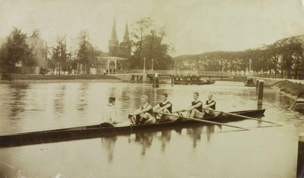 In het Rijn-Schiekanaal ligt een boot met de Oude Vier van Laga, v.l.n.r. trainer A.P. Petrie en roeiers J. Deking Dura (slag), F. Brandt, H. Tromp en F. Beukema, 1897, foto Henri de Louw. (TMS 7031)